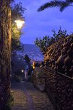 narrow street inside vintage medieval fortress on the banks of the Mediterranean sea, the evening dark blue sky stock photo