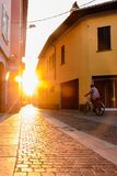 Narrow street between italian houses in old town in the evening rays of the setting sun., Toning.Passing by a woman on a bicycle. Narrow street between italian Stock Images