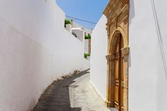 Narrow street in Lindos town on Rhodes island, Dodecanese, Greece. Beautiful scenic old ancient white houses with flowers. Famous stock photos