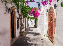 Narrow street in Lindos town on Rhodes island, Dodecanese, Greece. Beautiful scenic old ancient white houses with flowers. Famous royalty free stock photo