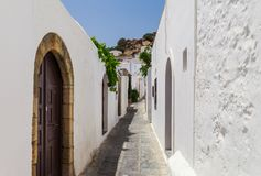 Narrow street in Lindos town on Rhodes island, Dodecanese, Greece. Beautiful scenic old ancient white houses with flowers. Famous royalty free stock photography