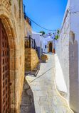 Narrow street in Lindos town on Rhodes island, Dodecanese, Greece. Beautiful scenic old ancient white houses with flowers. Famous. Tourist destination in South stock photo