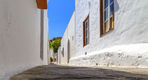 Narrow street in Lindos town on Rhodes island, Dodecanese, Greece. Beautiful scenic old ancient white houses with flowers. Famous. Tourist destination in South royalty free stock photos