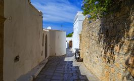 Narrow street in Lindos town on Rhodes island, Dodecanese, Greece. Beautiful scenic old ancient white houses with flowers. Famous. Tourist destination in South royalty free stock images