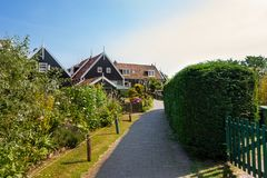 Narrow street of Marken houses, Netherlands, Europe. Green gardens and blue sky on a sunny day at sunset royalty free stock photo