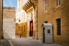 Narrow street of Mdina, Malta. MDINA, MALTA - MARCH 10 2017: Narrow street of ancient Silent City with Saint Dorothys Convent old building and Police box Stock Images