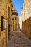 "The narrow street of Mdina, the old capital of Malta. MDINA, MALTA - JULY 29, 2015: The narrow medieval stone paved street with the restaurant ""Medina"" in Stock Photos"