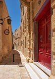 The narrow street of Mdina, the old capital of Malta. The narrow medieval stone paved street with red door and street light in the Mdina, the old capital of Stock Photography