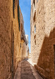 The narrow street of Mdina, the old capital of Malta. In the surroundings of limestone walls. The narrow medieval stone paved street of Mdina, the old capital Royalty Free Stock Image