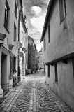 Narrow street with medieval European architecture and cobblestone pavement, Old Riga Stock Image