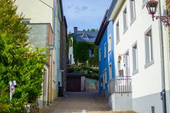 Narrow street in middle of Clervaux, in Luxembourg, with typical houses at both sides.  stock photo