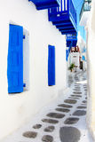 Narrow street in Mykonos. White washed houses and blue windows of a narrow street typical for mykonos Stock Photos