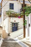 Narrow street in Neorio town on Poros island, Greece. Old white. House with blue door and flowers Royalty Free Stock Photos