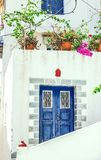 Narrow street in Neorio town on Poros island, Greece. Old white. House with blue door and flowers Royalty Free Stock Photo
