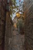 Narrow street in the old Budva night with vintage. Very narrow passage of the stone walls, vintage lantern illuminates the street Stock Photography