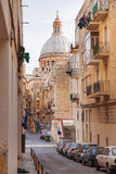 Narrow street with old fashioned balcony, carved stone walls and the St. Pauls Cathedral at the end of street. Malta. Royalty Free Stock Image