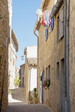 Narrow street with old houses and laundry in south Europe Royalty Free Stock Photo