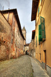 Narrow street among old houses in Saluzzo, Italy. Royalty Free Stock Photos