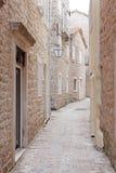 Narrow street of old stone city Stock Photos