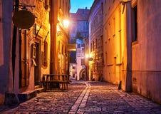Narrow street of Old town with Night lantern lamps. Narrow street of Old town with Night illumination. Czech Krumlov. Czech Republic. Shining lanterns at walls royalty free stock photo