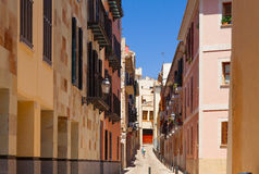 Narrow street in the old town with a person silhouette in the end. Majorca, Spain Royalty Free Stock Photos