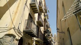 Narrow street with old urban architecture of european city. Action. Walls of houses are made of brown stone in old