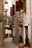Narrow street with opened shutters on windows. Royalty Free Stock Images