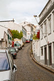 Narrow street with the parked cars Stock Photos
