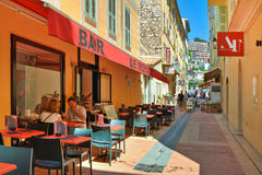Narrow street with restaurants in Menton. Stock Photo
