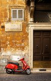 Narrow street in Rome with a typical red vespa scooter on a cobblestone street Stock Photography