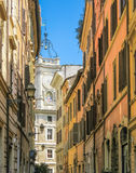 Narrow street of Rome and white church with bells. Narrow street of Rome in warm colors and white church with three bells and big clock, focus is on church Stock Image
