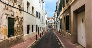 Narrow street at siesta time, no people. Narrow street without people in Menorca, Spain Royalty Free Stock Images
