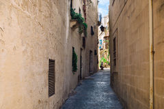 Narrow street in south Europe with residential buildings and motorbike. Royalty Free Stock Photography