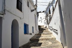 Narrow street with steps in Frigiliana, Spanish white village Andalusia. Beautiful and charming with its narrow streets and paths white village Frigiliana, close Royalty Free Stock Photo