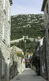 Narrow street in Ston with Great Wall in background in Ston, Croatia. Narrow street in Ston with Great Wall in background in Ston, Dubrovnik - Neretva, Croatia Royalty Free Stock Image