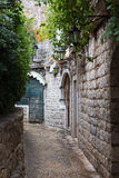 The narrow street in the stone fortress with lanterns. On a wall Stock Photography