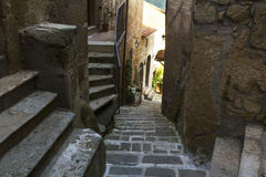 Narrow street with stone stairs in a town from Tuscany Stock Image