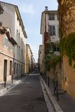 Narrow Street with Stucco Buildings. A narrow street with stucco buildings in gold, cream and tan. Vines grow along the sides of the buildings. Photographed in Stock Photo