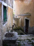 Narrow street with traditional old well in Volosko village in Croatia Royalty Free Stock Photography