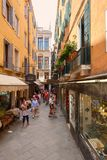 Narrow street with typical shops and restaurants in Venice. VENICE,ITALY - JULY 26,2017 : Narrow street with typical shops and restaurants in Venice Stock Image