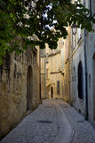 Narrow street in Uzes, France. Narrow lanes surround the castle in the Languedoc village of Uzes. Originally Ucetia, Uzès was a small Gallo-Roman oppidum, or Royalty Free Stock Photos