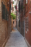 Narrow Street in Venice. Image of a typical narrow street between walls of houses in Venice Royalty Free Stock Photo