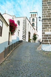 Narrow street and white church with flowers Stock Photos