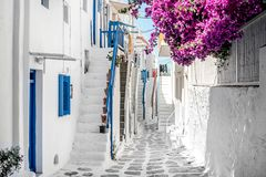 Narrow street with white houses, Greece. Beautiful narrow street with white houses in Mikonas island, Greece. Traditional narrow street with white facedes of Stock Photography