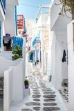 Narrow street with white houses, Greece. Beautiful narrow street with white houses in Mikonas island, Greece. Traditional narrow street with white facedes of Stock Photo