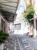 Narrow street with white houses, Greece. Beautiful narrow street with white houses in Mikonas island, Greece. Traditional narrow street with white facedes of Royalty Free Stock Photo