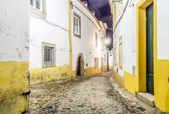 Narrow street with white and yellow houses in Evora, Alentejo, P. Narrow street with white and yellow houses by night in Evora, Alentejo, Portugal Royalty Free Stock Photography