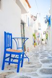 The narrow streets with blue balconies, stairs, white houses and flowers in beautiful village in Greece. Beautiful architecture building exterior with cycladic Royalty Free Stock Photos