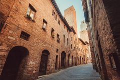 Narrow streets between brick houses of the ancient town of Tuscany. Historic San Gimignano. UNESCO World Heritage Site. Narrow streets between brick houses of royalty free stock photos