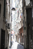 The narrow streets of the city of Genoa Italy. Old cobblestone road in the window grilles. Beautiful Perspective Lane. A good plac Stock Photography